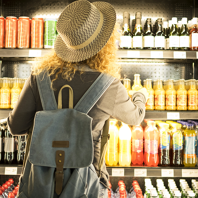 travel-woman-viewed-from-back-choosing-beverage-in-FRX3WK4